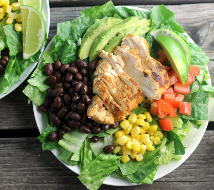 Southwest chicken salad topped with corn, tomatoes, black beans, avocados, and ranch dressing