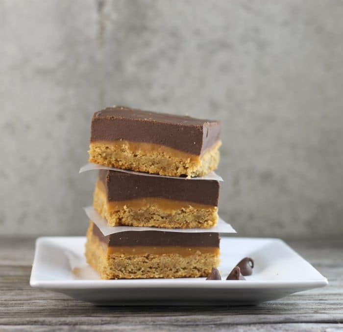 Peanut Butter Caramel Bars with a peanut butter cookie crust topped with a gooey caramel filling on top of all this a thick layer of chocolate peanut butter frosting.