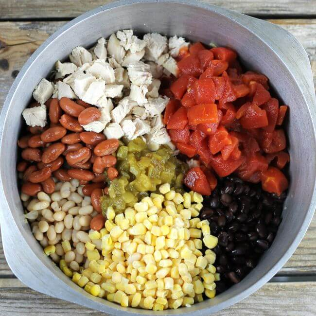Beans, corn, chilies, and chicken are added to the Dutch oven.