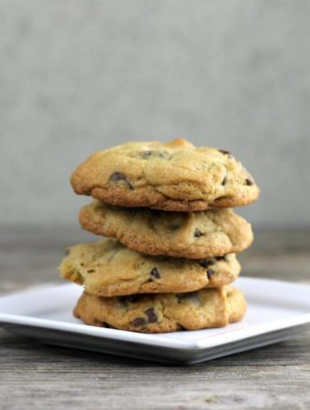 Stacked chocolate chip cookies on a white plate.