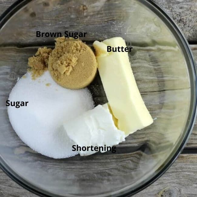 Butter, shortening, sugar, and brown sugar in a glass bowl.