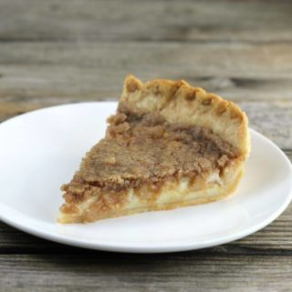 Side angle view of a slice of apple sour cream pie on a white plate.