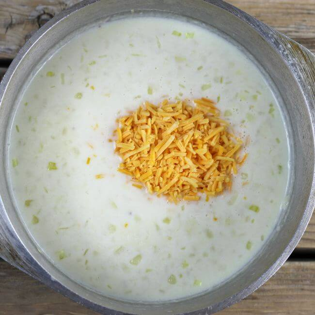 Shredded cheese is added to the soup.