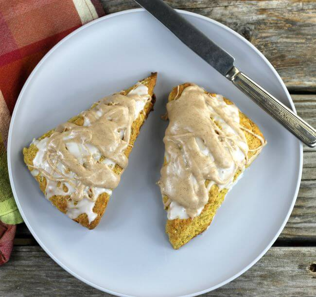 Two pumpkin scones on a gray plate with a knife on the side.