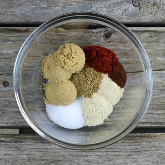 Cumin, brown sugar, onion powder, garlic powder, and paprika in a glass bowl.