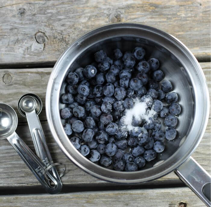 Blueberries and sugar in a saucepan with measuring spoons