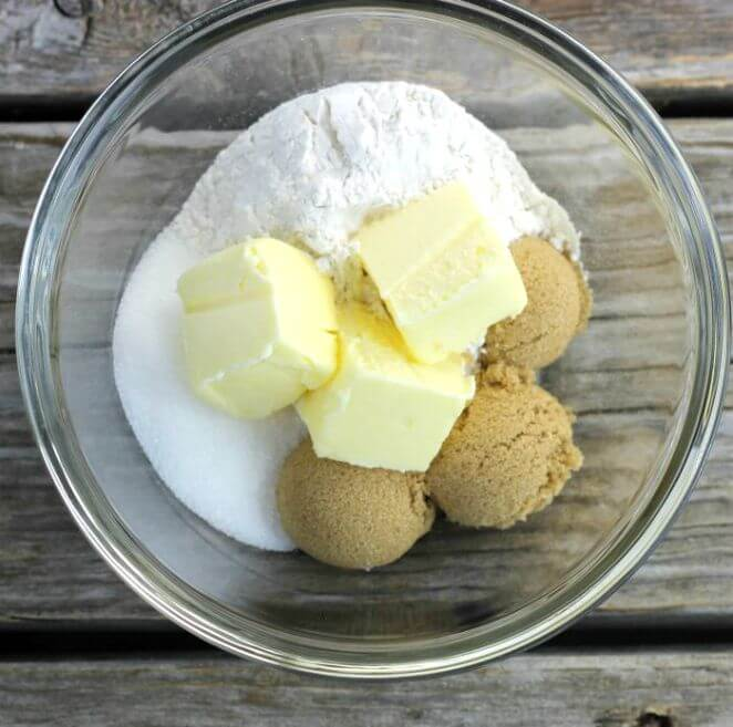 sugar, brown sugar, flour, and butter in glass bowl