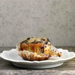 unwrapped blueberry muffin on a white plate