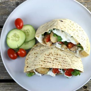 A Pita stuffed with tomato, chicken, and lettuce with cucumber and cherry tomatoes on the side.