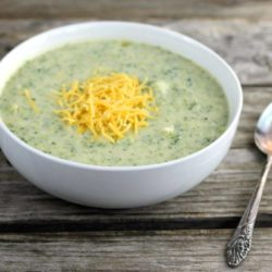 Side angle view of cheese broccoli soup in a white bowl.
