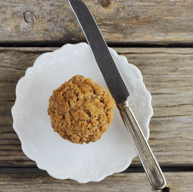 Looking down at a muffin on a white plate with a knife on the side.