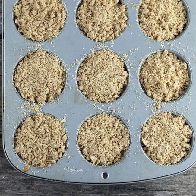 Muffin batter with crumb topping in muffin tins.