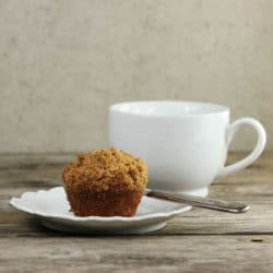Side view of a muffin on a white plate with a coffee cup behind.
