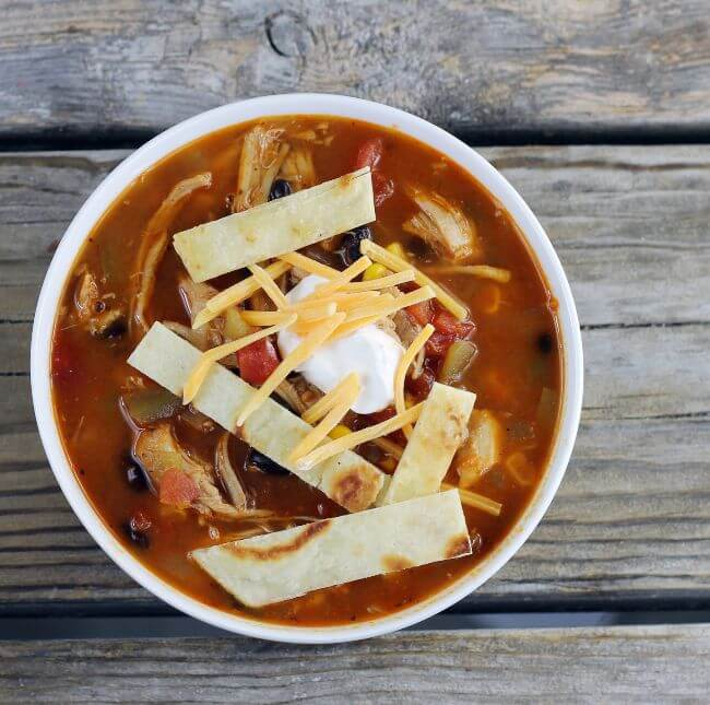 Overhead view of a bowl of southwest soup with cheese tortilla strips and sour cream on top.