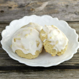 Frosted lemon cookies on a white plate.