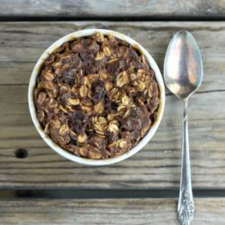 Looking down at a baked oatmeal in a ramekin with a spoon on the side.