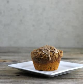 Side view of a muffin on a white square plate.