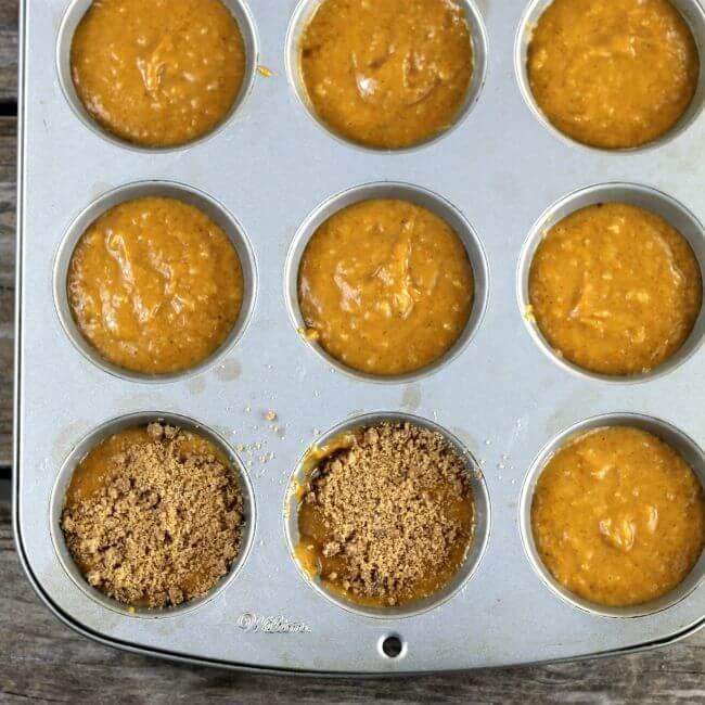 Pumpkin muffin batter in muffin tins.