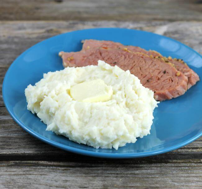 A scoop of mashed potatoes on a blue plate with a slice of meat.