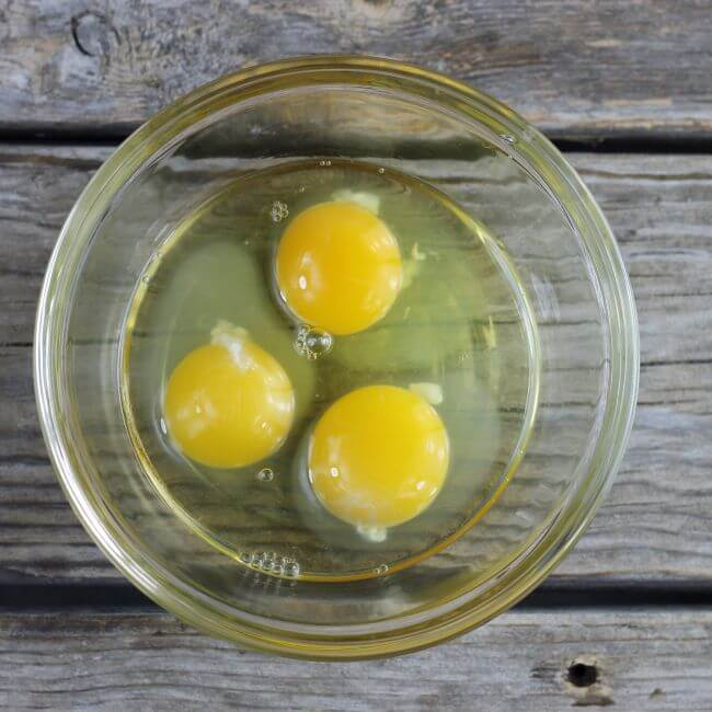 Three eggs in a glass bowl.