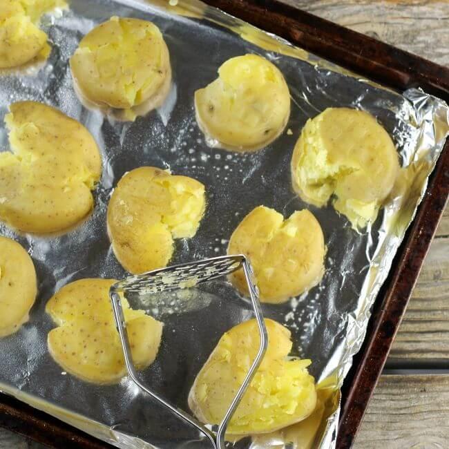 A potatoe masher with baby potatoes on a baking pan.