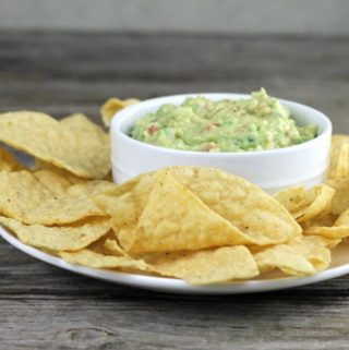 The dip in a white dish with chips on a plate.
