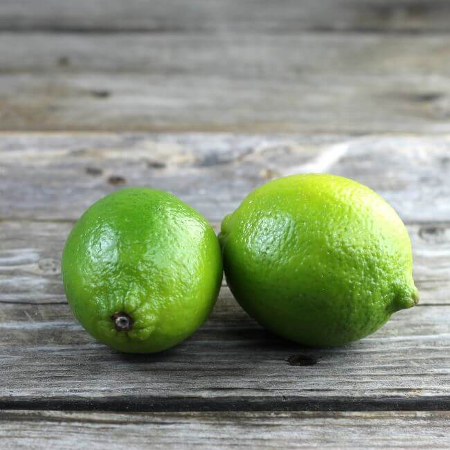 Two limes set on a table.