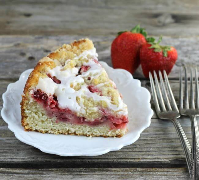 Side angle view of a slice of coffee cake with forks and strawberries on the side.