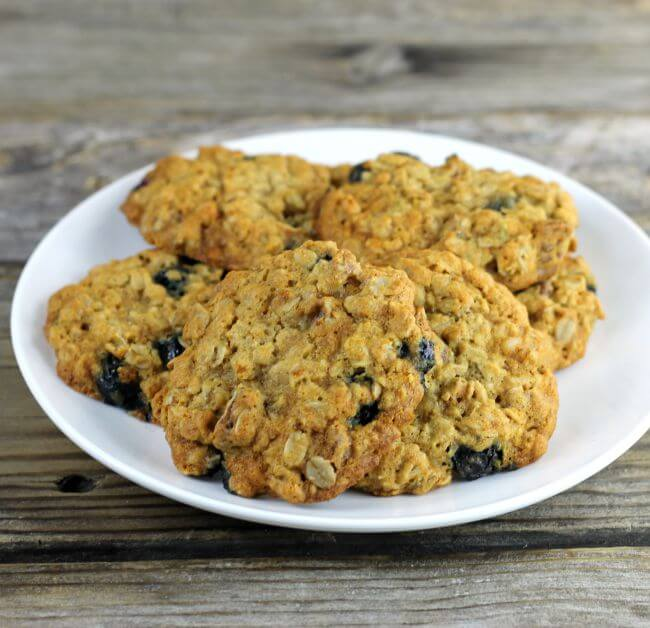 A white plate piled with oatmeal blueberry cookies.