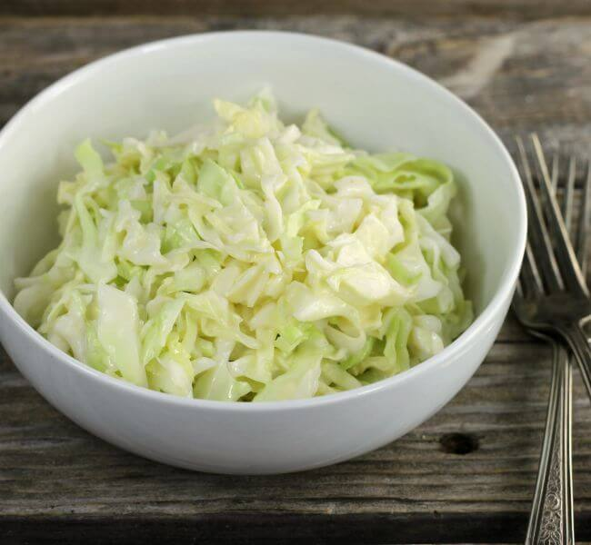 Side angle view of coleslaw in a white bowl.