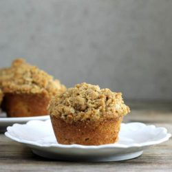 A side view of a muffin on a white plate with more muffins in the back.