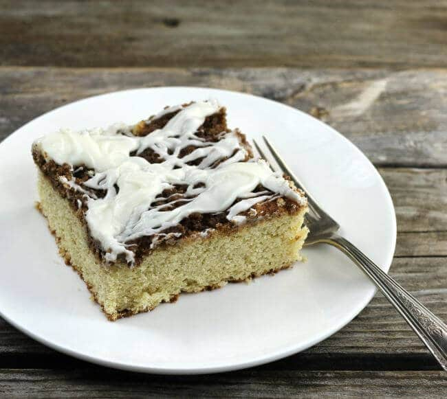 A slice of coffe cake on a white plate with a fork on the side.