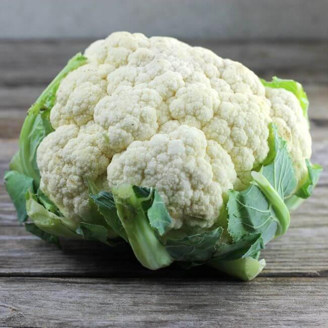 A head of cauliflower on a table.