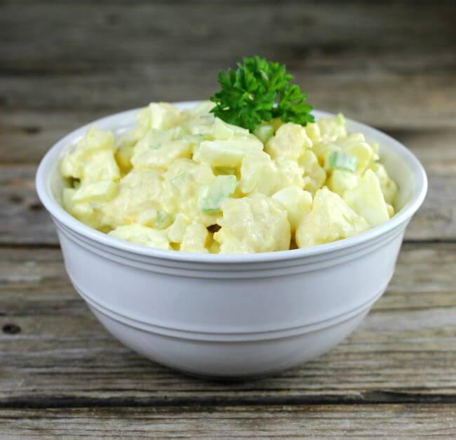 Side angle view of a white bowl with cauliflower potato salad.