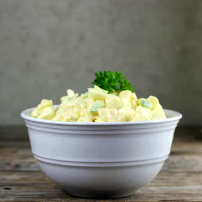 Side view of a white bowl filled with cauliflower potato salad.