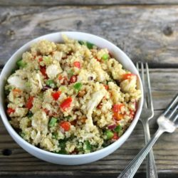 Side angle view of a white bowl with quinoa and vegetables with two forks on the side.