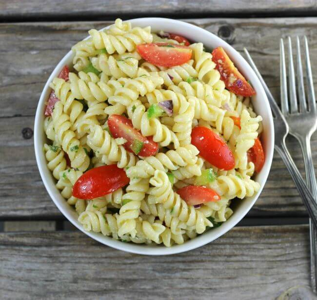 Looking down at a bowl of pasta with tomatoes and green peppers.