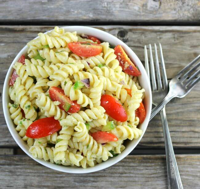 Over looking a bowl of pasta with forks on the side of the bowl.