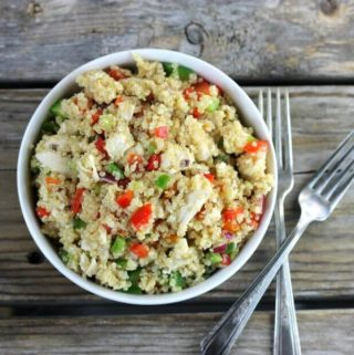 Over lookig a bowl of quinoa salad with two forks on the side.