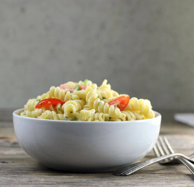 Side view of a white bowl filled with pasta.