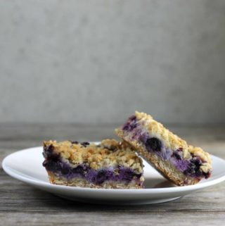 Side view of blueberry bars on a white plate.