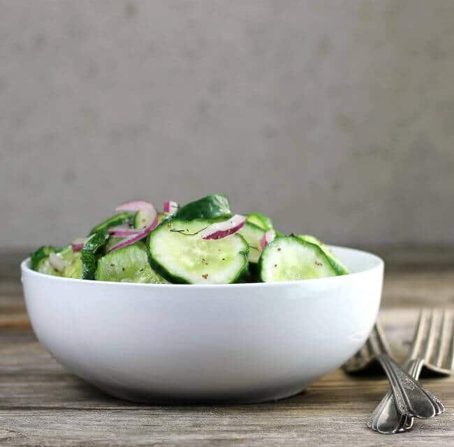 Side view of cucumber salad in a white bowl with forks on the side.