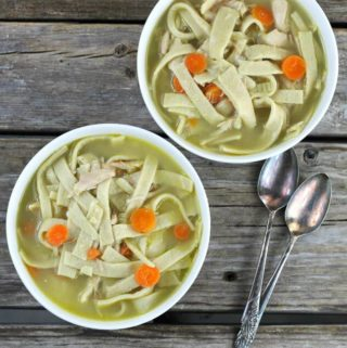Overhead view of two bowls of chicken soup in white bowls.