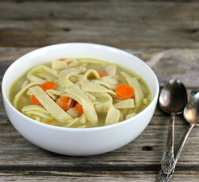 Side view of chicken noodle soup with spoons on the side.