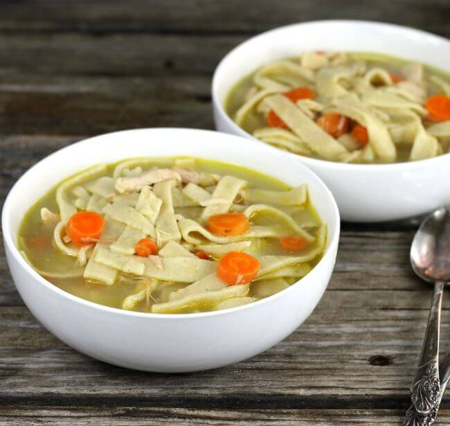 Side view of two bowls of chicken noodle soup.