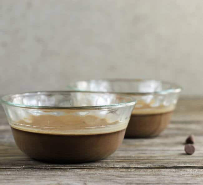 A side view of two bowls of baked chocolate pudding.