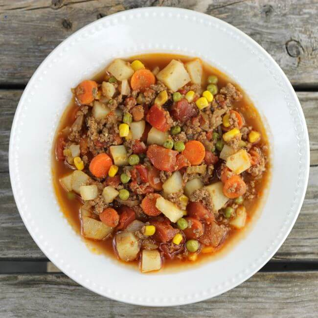 Easy hamburger stew in a white bowl.
