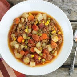 Easy hamburger stew in a white bowl with a napkin on the left side and a spoon on the right side of the bowl.