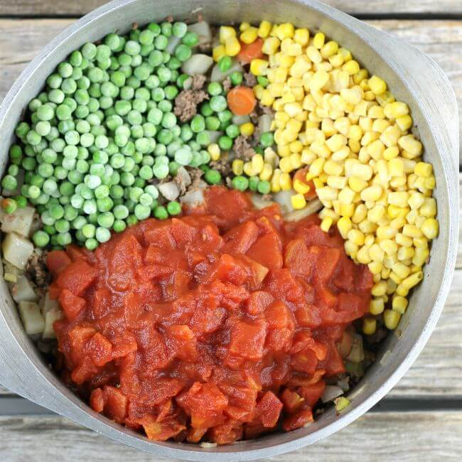Peas, corn, and tomatoes added to the hamburger stew in a Dutch oven.