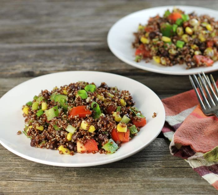 Black bean quinoa salad a hearty and healthy salad filled with chopped tomatoes, green pepper, and green onions.